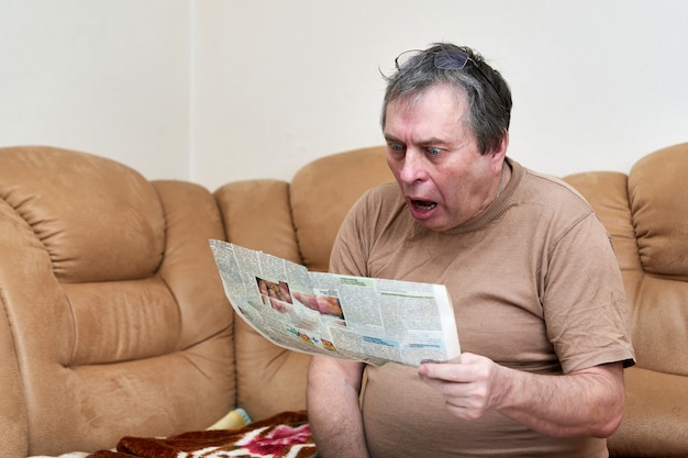 A man in age is reading the news in the newspaper while sitting on the couch