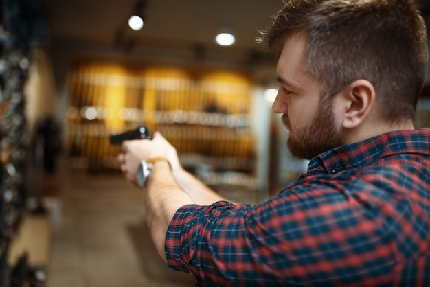 Man aims with new handgun in gun shop. male person buying pistol for security in weapon store, selfdefence and sport shooting hobby