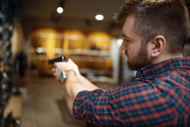 남자는 총기 상점에서 새로운 권총을 목표로합니다. 무기 상점, 자기 방어 및 스포츠 촬영 취미에서 보안을 위해 권총을 사는 남성 사람
