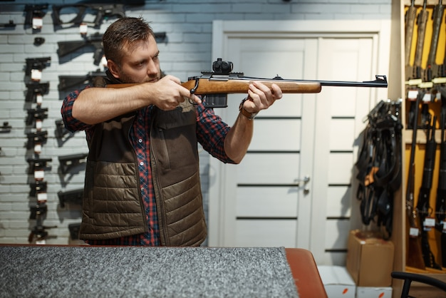 Человек целится из новой винтовки в оружейном магазине. мужчина покупает оружие в магазине, охота и спортивная стрельба хобби