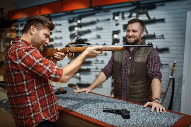 Man aims with new rifle, seller at counter in gun shop. male person buying weapon in store, hunting and sport shooting hobby