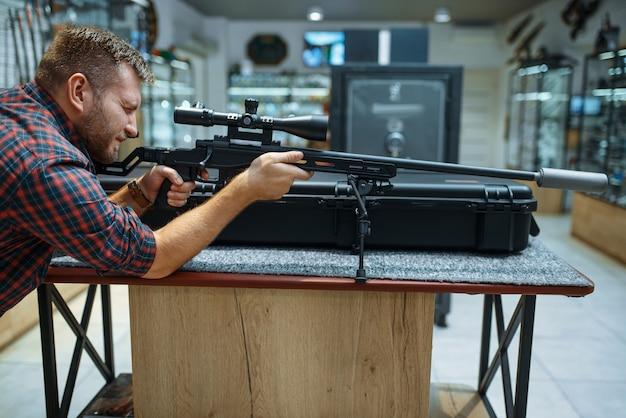男は銃専門店で狙撃ライフルを狙う