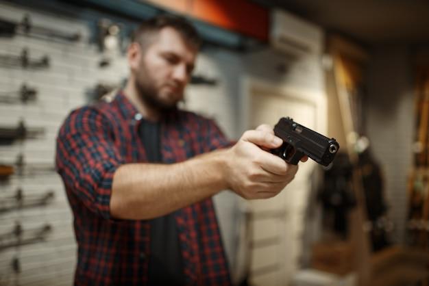 남자는 총기 상점에서 두 개의 권총으로 목표로합니다.