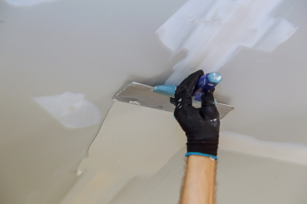 Man aligning a wall with spatula working with putty and spatula wall