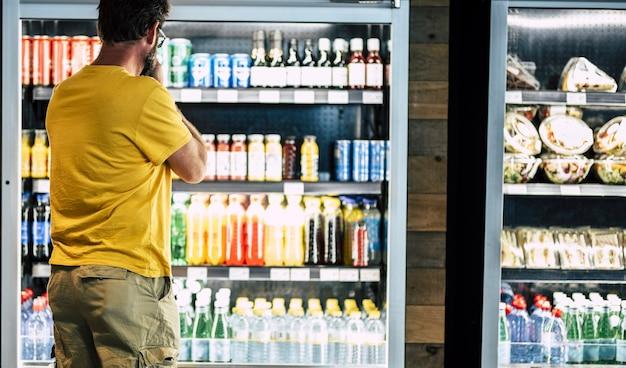 Человек один и изолирован в супермаркете или минимаркете, выбирая напиток или закуску в большом холодильнике с большим количеством продуктов