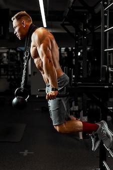 アスリートがジムに従事し、腕の筋肉の上腕二頭筋の黒い背景に運動をしている男性。高品質の写真。