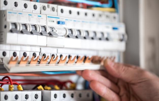 男、ヒューズ付きの配電盤で働く電気技術者。電気機器の設置と接続。閉じる。