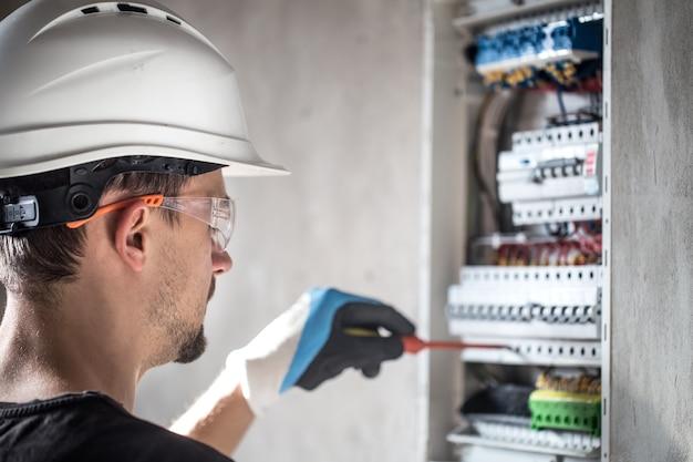 Мужчина, электрик работает в распределительном щите с предохранителями. монтаж и подключение электрооборудования.
