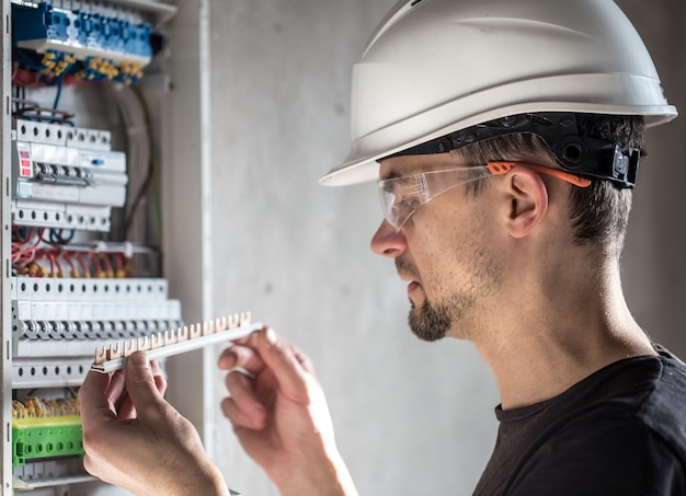 男、ヒューズ付きの配電盤で働く電気技術者。電気機器の設置と接続。