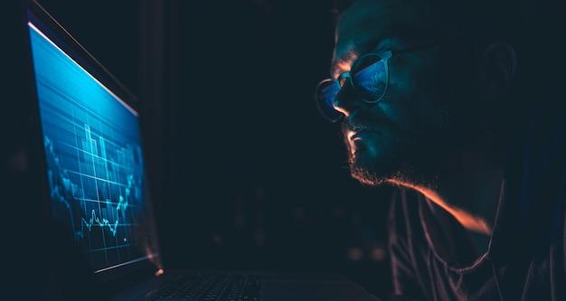 Un uomo che analizza i dati finanziari dei grafici del mercato azionario su una scheda elettronica