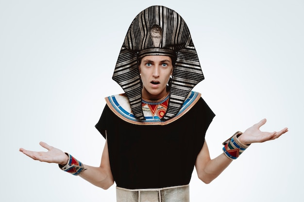 Man in ancient egyptian costume confused raising arms having no answer on white
