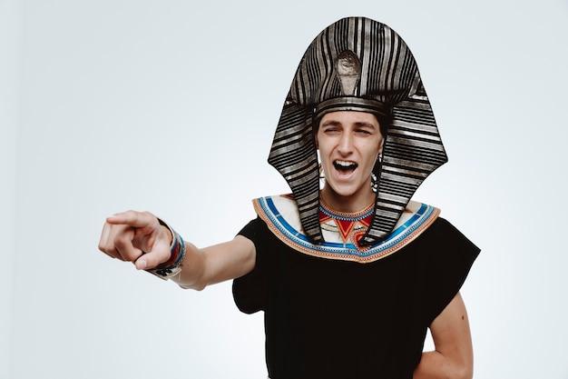 Uomo in antico costume egiziano pazzo felice che ride puntando con il dito indice a qualcosa su bianco