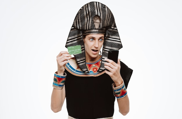 Man in ancient egyptian costume holding smartphone and credit card being amazed and surprised on white