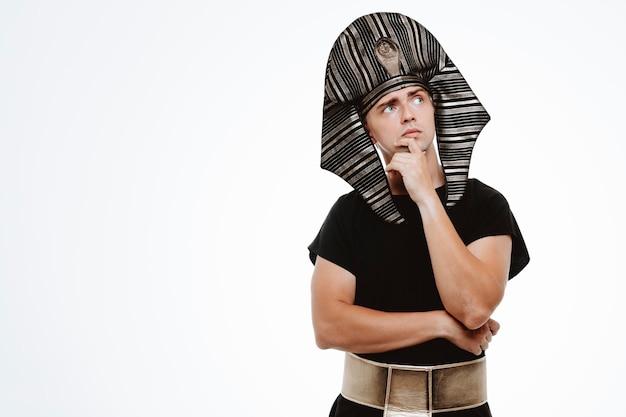 Uomo in antico costume egiziano che guarda in alto con espressione pensierosa pensando con la mano sul mento su bianco