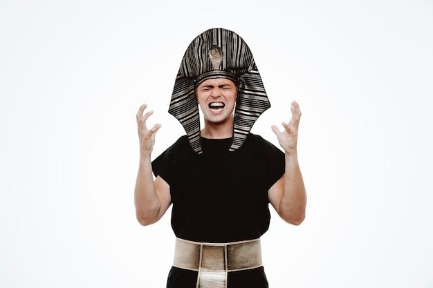 Uomo in antico costume egiziano che alza le braccia arrabbiato e frustrato urlando su bianco