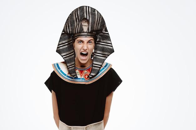 Uomo in antico costume egiziano che grida e urla arrabbiato e frustrato su bianco