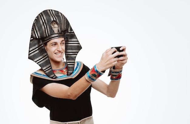 Uomo in antico costume egiziano che si fa selfie utilizzando lo smartphone felice e positivo su bianco