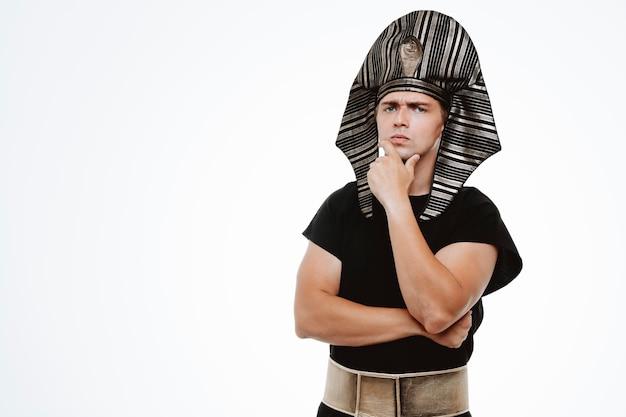 Uomo in antico costume egiziano con espressione pensierosa che pensa con la mano sul mento su bianco