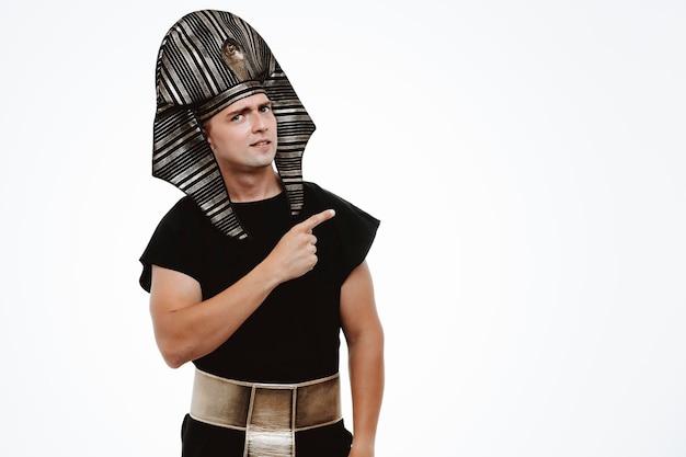Uomo in antico costume egiziano con sorriso sul viso che punta con il dito indice di lato su bianco