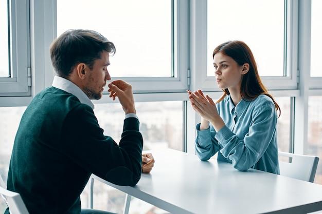 Мужчина и женщина сидят за столом, разговаривают, ссорятся друг с другом, настоящая ссора, бытовые проблемы
