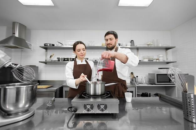男性と女性の菓子職人は、ケーキを埋めるために鍋にベリークリを準備します