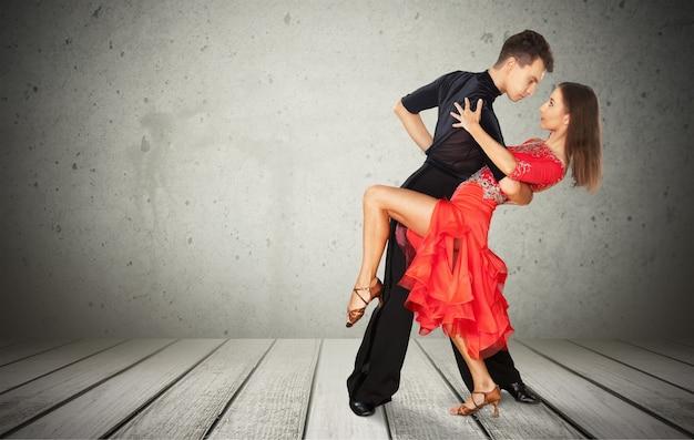 회색 벽 배경에서 살사 춤을 추는 남자와 여자