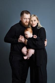 남자와 여자는 그들의 팔에 아기를 안고 있습니다. 아이를 낳은 후 부부의 초상화. 젊은 가족