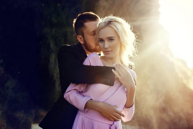 夕焼けの夏に美しい服を着て抱き締める男女。愛するカップルは、太陽の下で岩の上に立って、水しぶきの中で抱き合ったりキスしたりします。ピンクのドレス