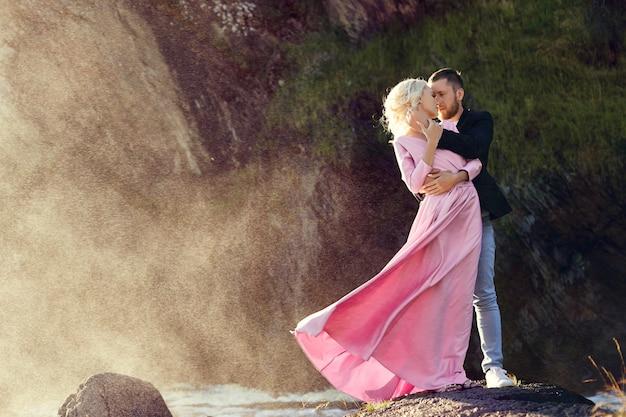 Мужчина и женщина обнимаются летом на закате в красивой одежде