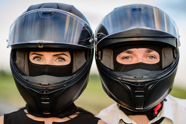 カメラを見ているオートバイのヘルメットの男と女。