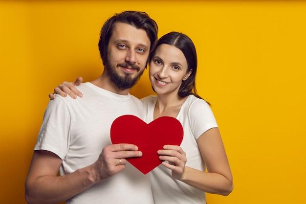 白いtシャツを着た男性と女性がバレンタインデーに紙のハートを保持します