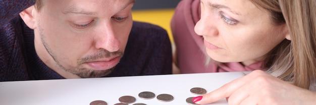男性と女性は、テーブルの家族の予算計画の概念のコインに腹を立てている