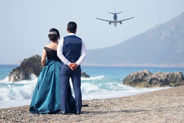 ビーチで出発する旅客機を見ている男性と女性