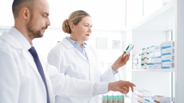 Мужчина и женщина-фармацевты, стоящие у полки с лекарствами