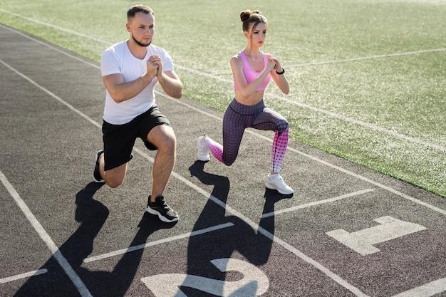 Мужчина и женщина занимаются спортом на стадионе летом, делая выпады