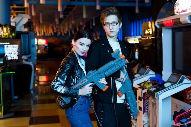 Мужчина и женщина играют на игровых автоматах, аттракционах в торговом центре