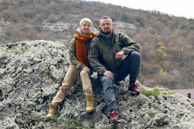 Мужчина и женщина сидят на скале осенью в теплой одежде