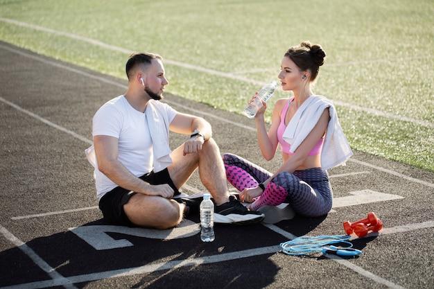Мужчина и женщина сидят на беговых дорожках после пробежки на стадионе летом, слушают музыку в наушниках