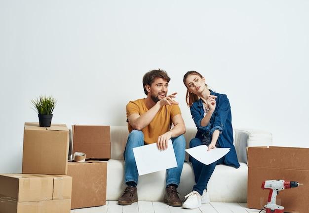 Мужчина и женщина сидят на диване в новой квартире
