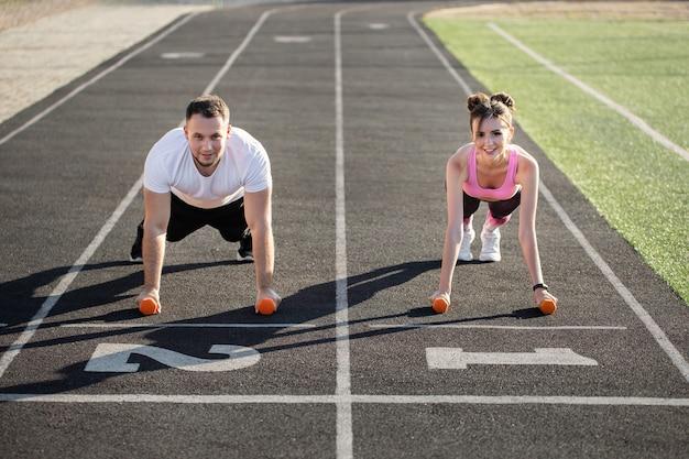 Мужчина и женщина тренируются с гантелями на стадионе летом. спортивный образ жизни