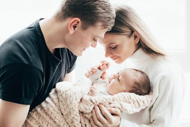 남자와 밝은 배경에 그녀의 팔에 아기를 가진 여자