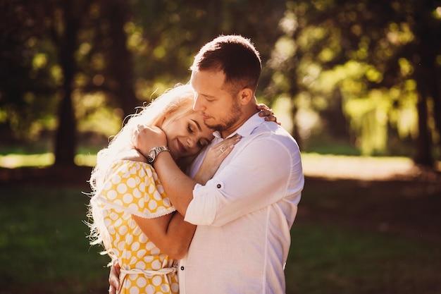 Мужчина и красивая женщина в желтом платье обнимать друг друга тендер