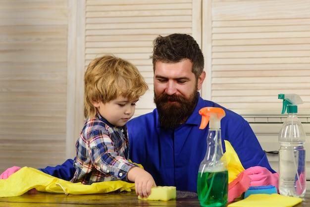 男と子が一緒に居間を掃除しているお父さんと息子をまぶしている