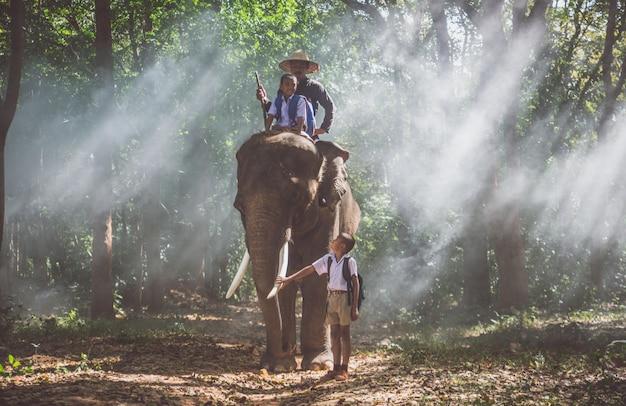 象とジャングルに行く男と子供たち、タイ北部のライフスタイルの瞬間