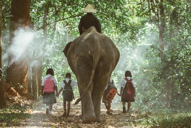 象とジャングルを行く男と子供たち、タイ北部からのライフスタイルの瞬間