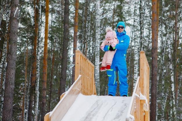 Мужчина и дочь стоят на деревянной горке. зимние русские забавы. яркая одежда, солнечные очки, высокая деревянная гора, сосновый бор.