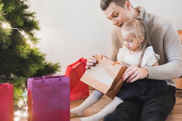 男と娘はクリスマスに贈り物を開く