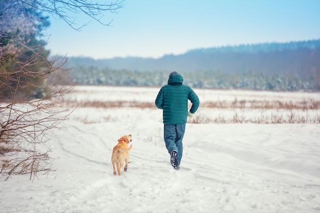 Человек и собака - лучшие друзья. мужчина с собакой бежит по заснеженному полю зимой
