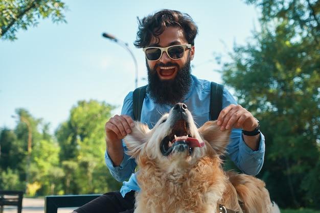 男と犬を楽しんで、遊んで、面白い顔を作る