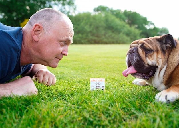 人と犬が公園の緑の芝生の上のおもちゃの家を見て